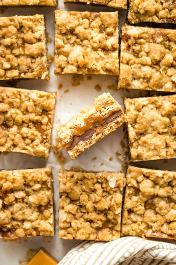 Close up of carmelita bars, with one turned on its side to show layers of gooey caramel and chocolate.