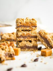 Stack of thick, chewy carmelita cookie bars, surrounded by extra chocolate chips and caramels.