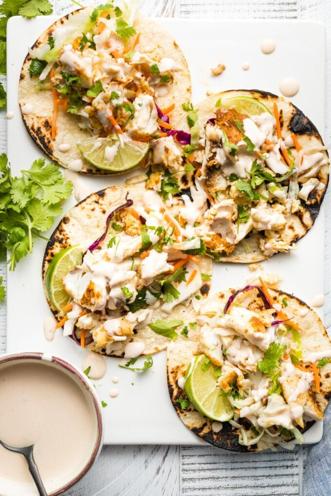 White plate with four fish tacos, ready to serve.