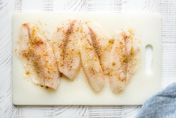 Seasoned tilapia on a cutting board.