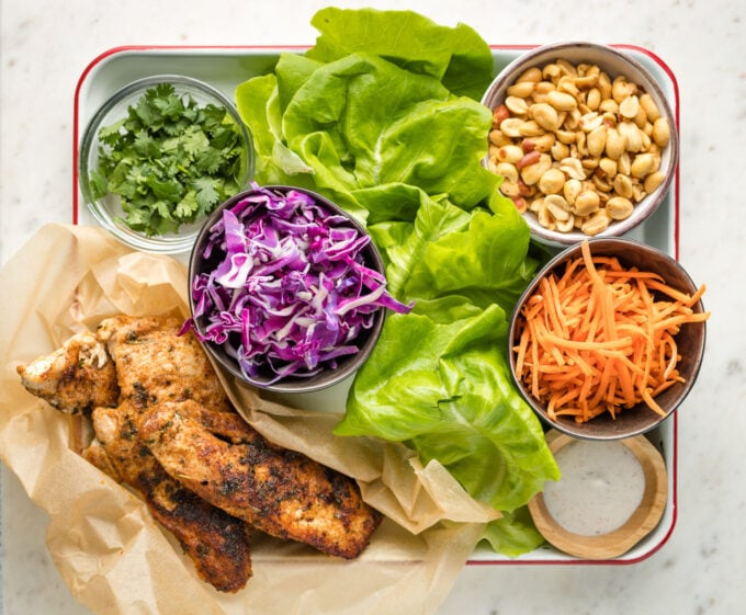 Lettuce, cabbage, jerk chicken, carrots, peanuts, and cilantro laid out in individual prep bowls.