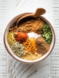 Small white bowl holding spices for Jamaican jerk seasoning.