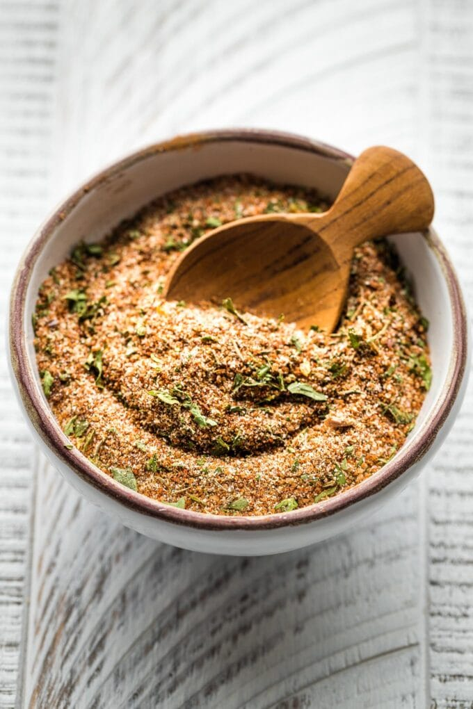 Small bowl with a wooden spoon scooping out Jamaican jerk seasoning.