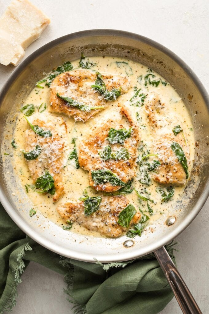 Skillet full of creamy chicken Florentine topped with grated Parmesan cheese.