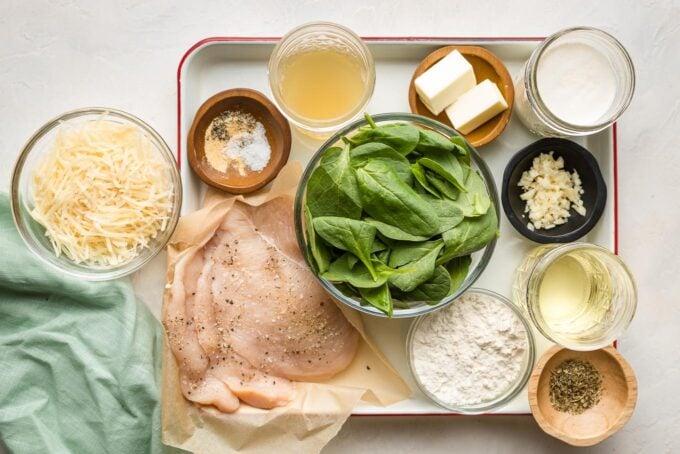 Ingredients arranged on a prep tray - chicken, Parmesan, spinach, flour, butter, garlic, cream, broth, seasonings.