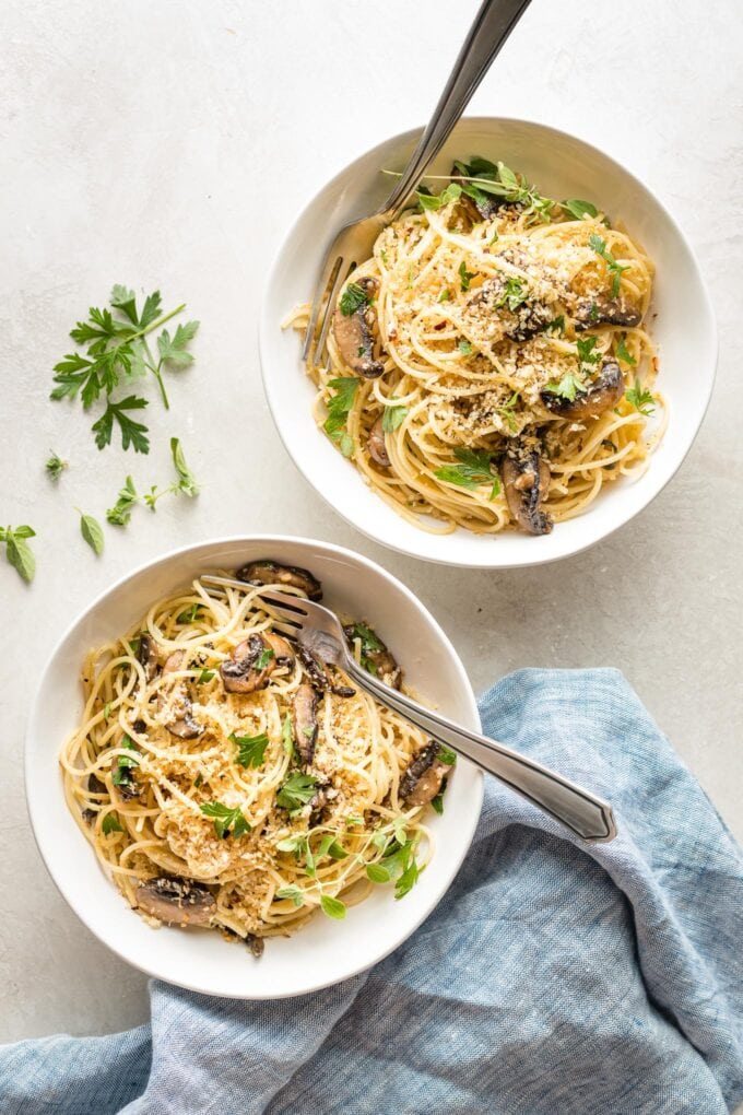 Two bowls of spaghetti with mushrooms, oregano, and toasted breadcrumbs, ready to dig in.