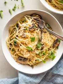 Bowl of garlic mushroom spaghetti with fresh oregano and toasted garlicky breadcrumbs.