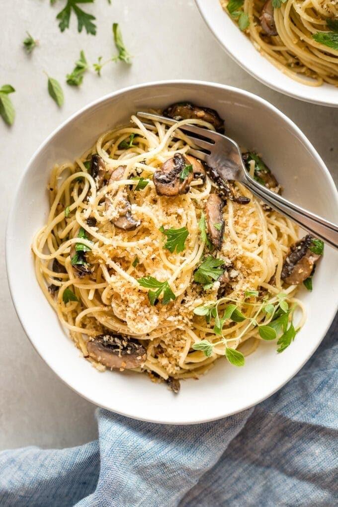 Bowl of garlic mushroom spaghetti with fresh oregano and toasted garlicky breadcrumbs.
