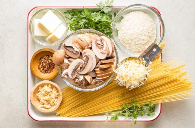 Prep bowls with ingredients: dried spaghetti, mushrooms, breadcrumbs, butter, oregano, parsley, garlic, salt, black pepper, red pepper flakes.