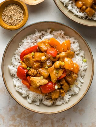 Bowls of pineapple chicken served with rice.