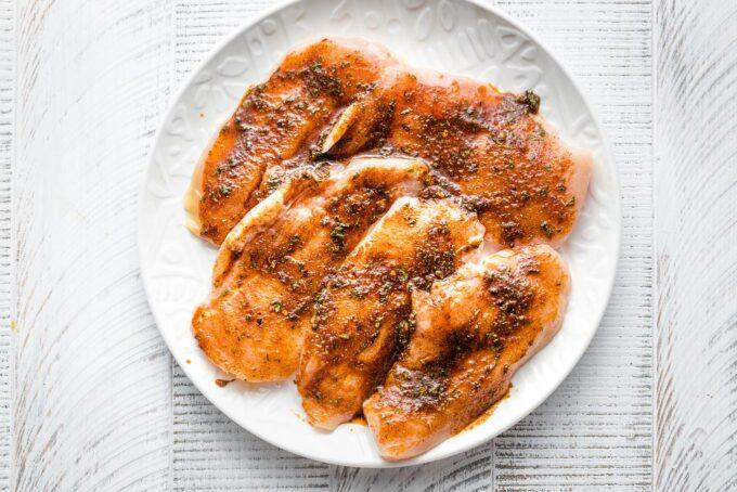 Seasoned raw chicken on a plate.