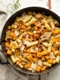 Roasted butternut squash pasta with rosemary and bacon in a skillet.