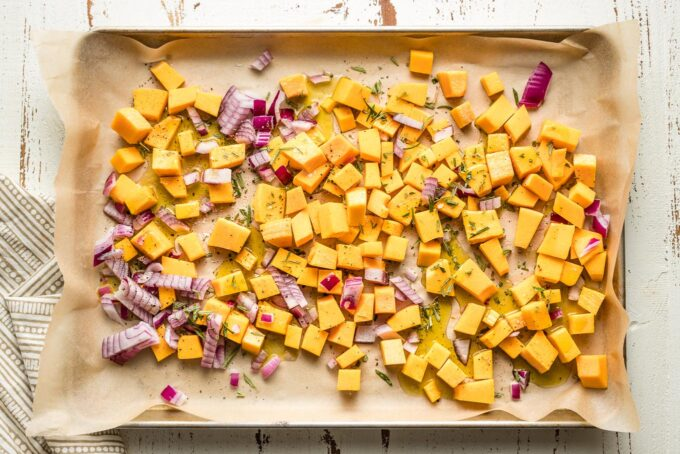 Baking sheet with squash, onion, and seasonings.