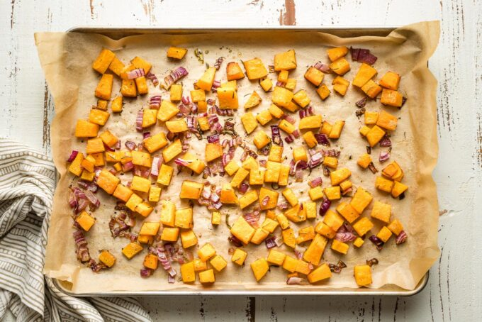 Baking sheet with roasted squash and onions.