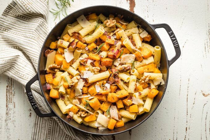 Skillet with pasta, squash, and extras added and tossed together.
