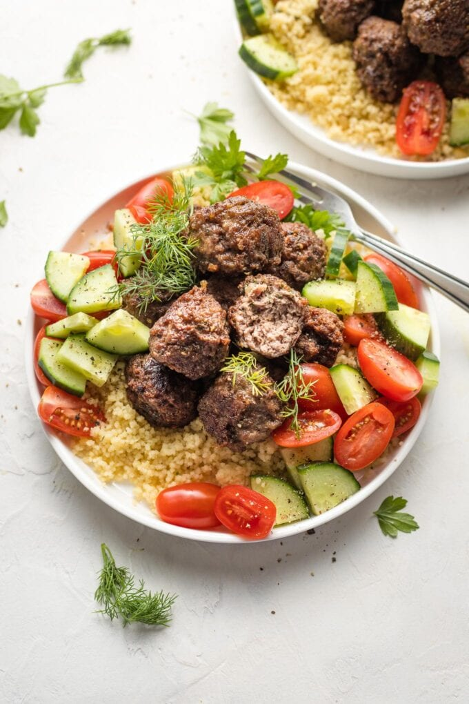 Close-up of lamb meatballs served with couscous and a tomato cucumber salad.