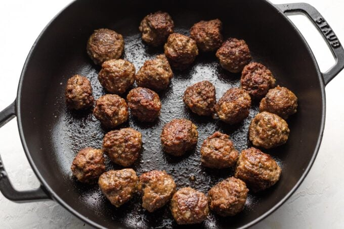 Cooked lamb meatballs in a skillet.