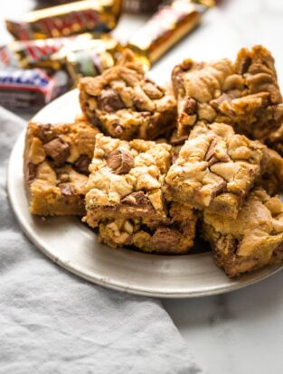 Blondies with candy bars mixed in, arranged on a small plate.