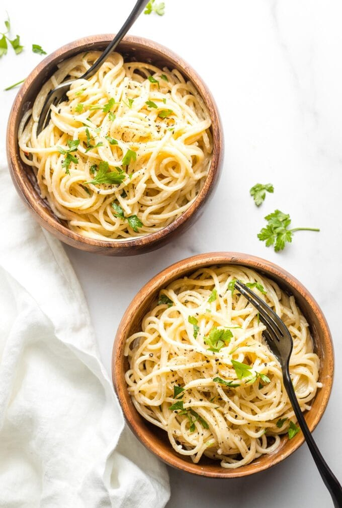 Two small wooden bowls with creamy garlic spaghetti.