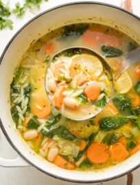 Ladle full of white bean and spinach soup with orzo.