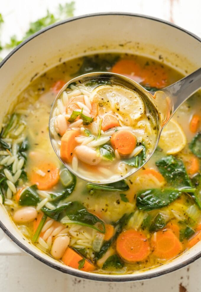 Large pot of white bean and spinach soup with orzo and lemon.