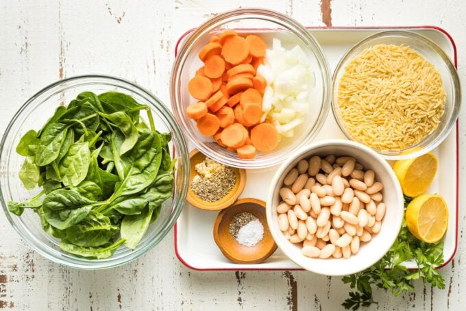 Prep bowls holding baby spinach, chopped carrots and onion, orzo, cannellini beans, and seasonings.