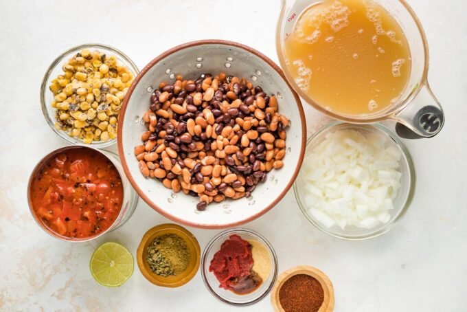 Beans, tomatoes, broth, corn, onions, and spices arranged in prep bowls.
