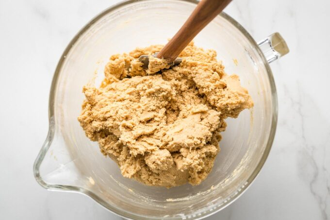 Clear mixing bowl full of peanut butter cookie dough.