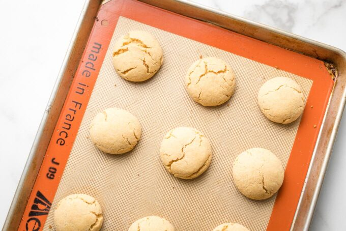 Baked peanut butter cookies, showing slight cracks on the tops.