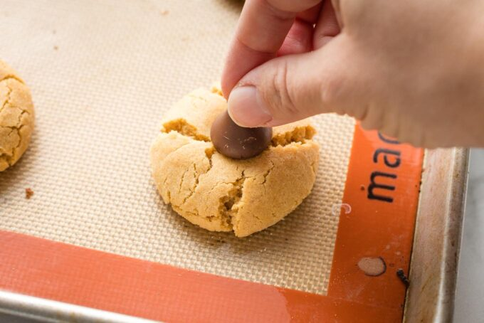 Hand pushing a Hershey's kiss into a just-baked peanut butter cookie to make a peanut butter blossom.