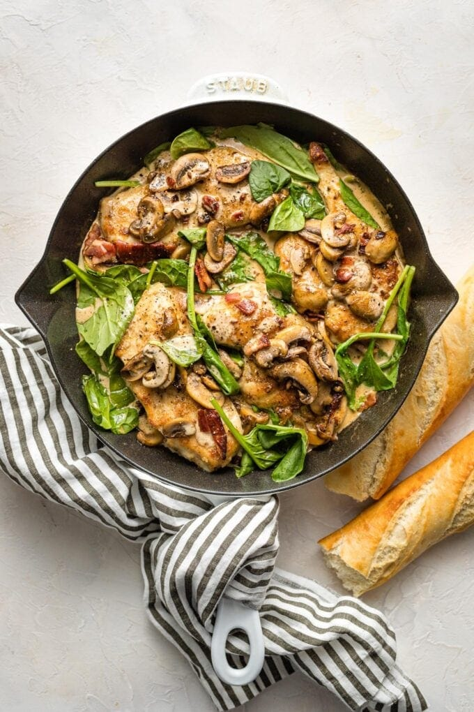 Creamy balsamic chicken with spinach and mushrooms cooked in a cast iron skillet.