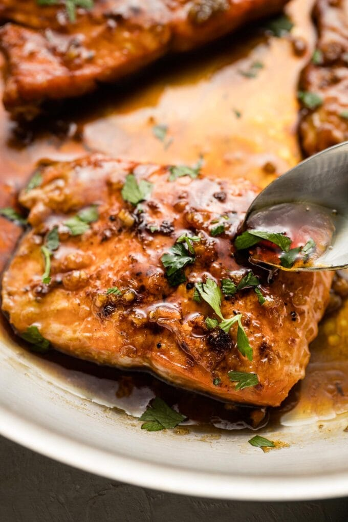 Close-up of a spoon pouring sauce over a salmon filet.