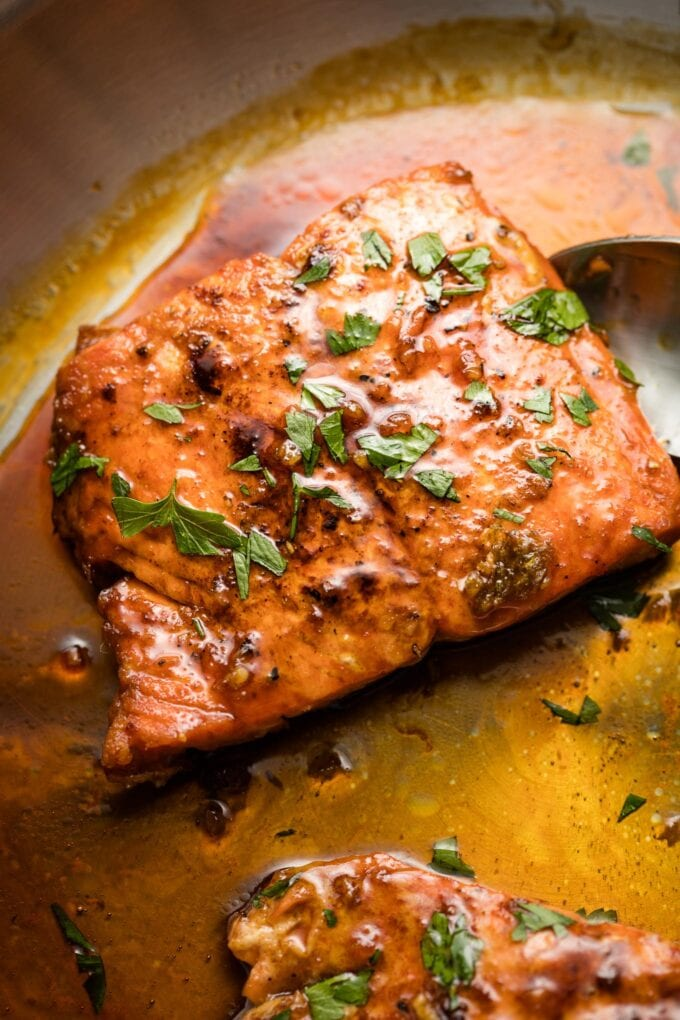 Close up of salmon in pan with honey garlic sauce.