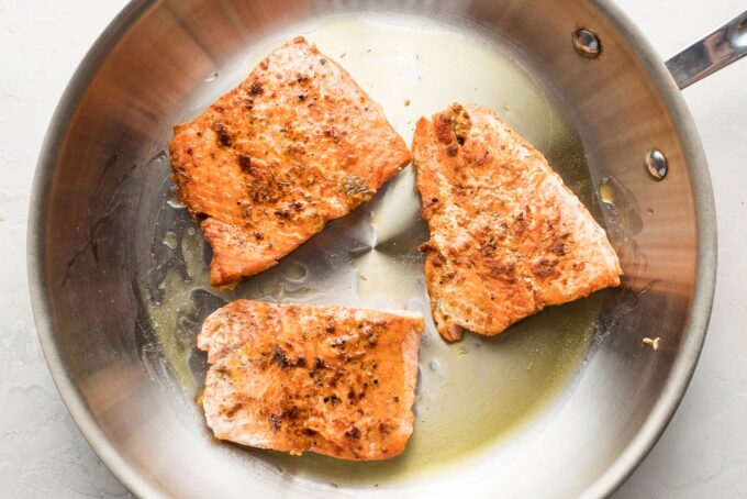 Cooked salmon filets in a pan.