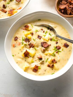 Bowl of potato cheddar chowder garnished with crumbled bacon and chives.