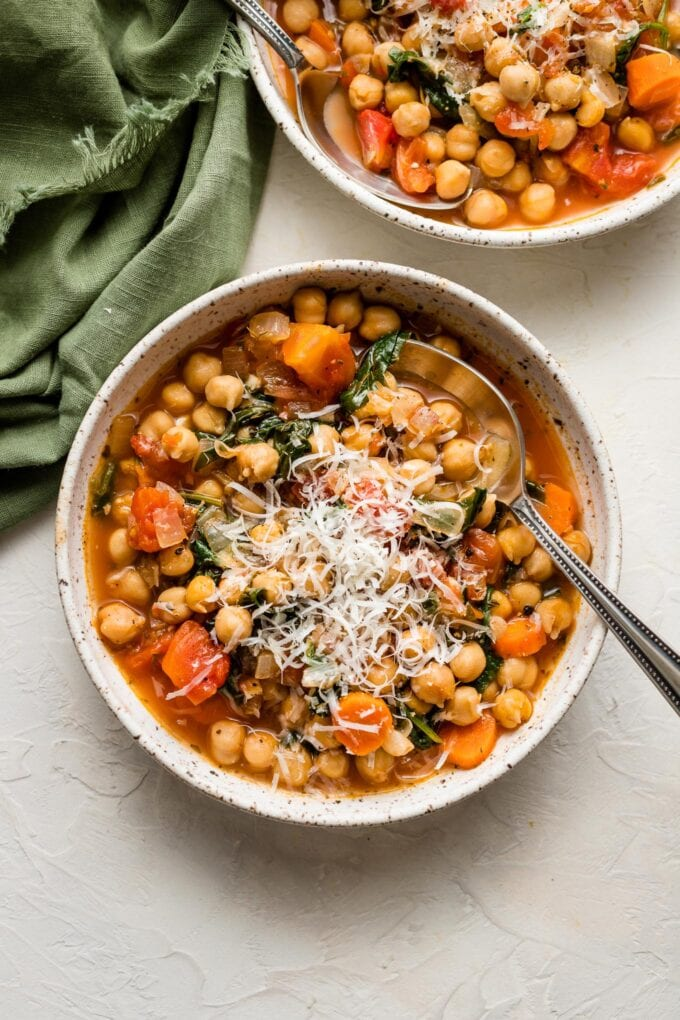 Bowls of chickpea stew served with fresh-grated Parmesan.