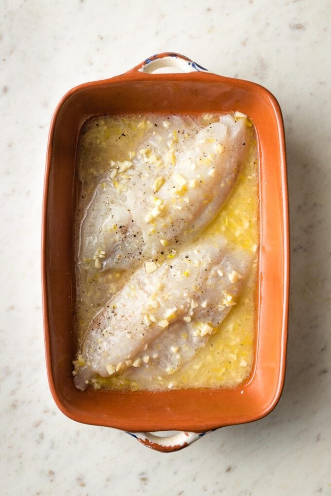 Butter poured over fish in pan.