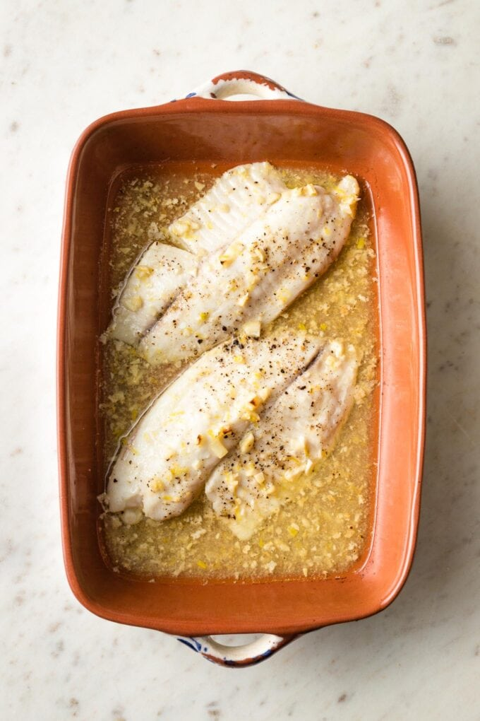 Baked tilapia with lemon butter sauce in pan.