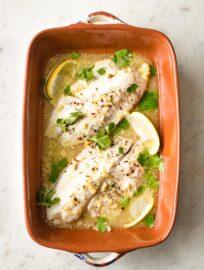 Baked tilapia with lemon in an earthenware pan.