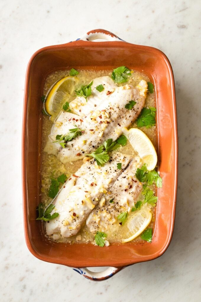 Baked tilapia with lemon in an earthenware pan.