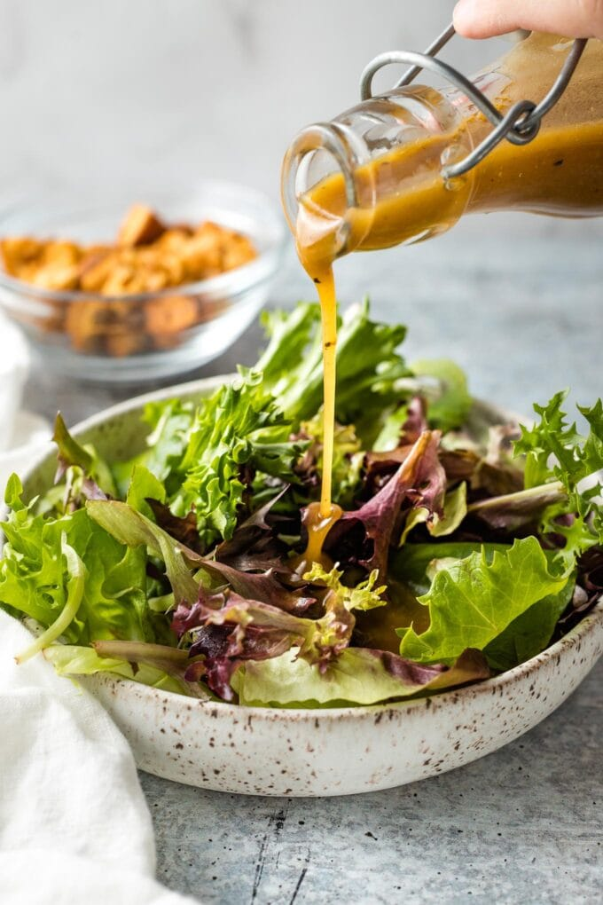 Dressing being poured on salad greens.