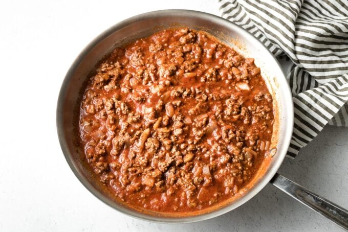 Seasoned beef in skillet with tomato sauce.