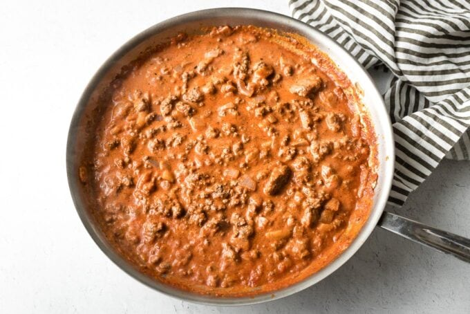 Beef, tomato sauce, and cream simmered in skillet.