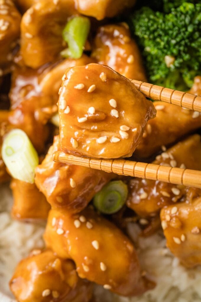 Close-up of a bite-sized piece of chicken coated in teriyaki sauce, held by a pair of chopsticks.