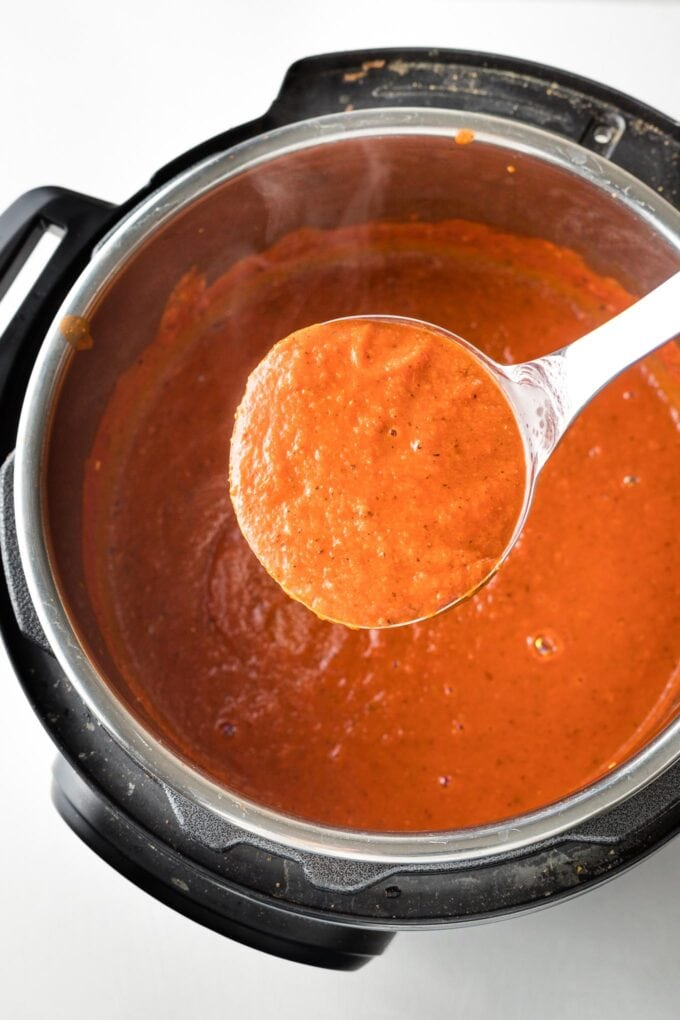 Ladle of smooth tomato soup held over full batch of soup in the bowl of an Instant Pot.