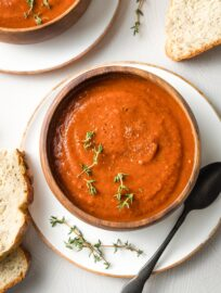 Bowls of tomato soup with slices of bread.