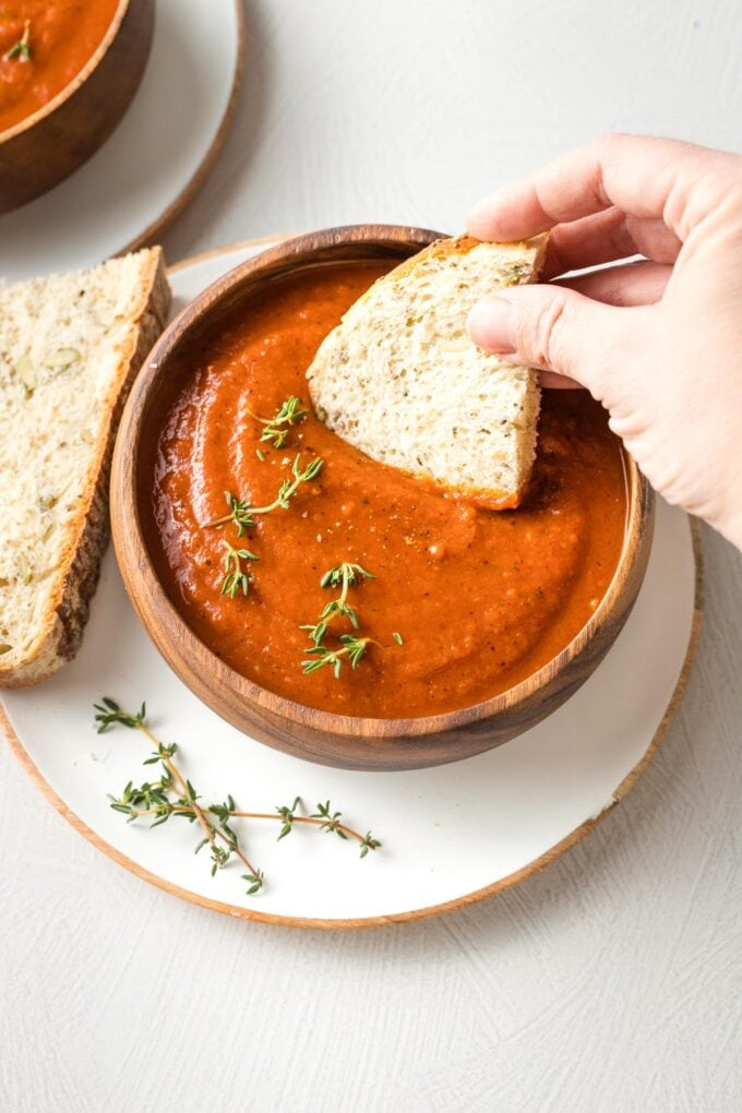 Hand dipping a slice of bread into a bowl of tomato soup.
