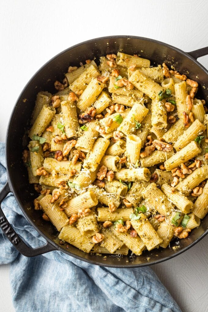 Deep cast iron skillet full of pesto rigatoni with Parmesan cheese on top.