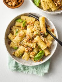 Bowls of rigatoni with pesto and toasted walnuts.