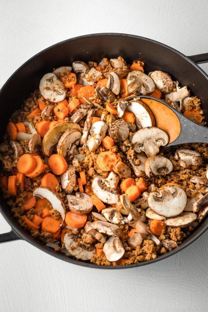 Veggies cooking in a deep skillet.